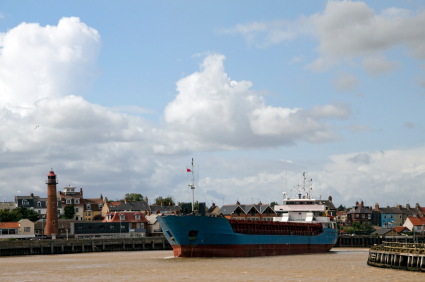 Cargo ship leaves Great Yarmouth harbour on River Yare at Gorleston